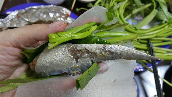 Cá nục hấp được cuốn trong bánh tráng với rau sống rồi chấm nước mắm nêm